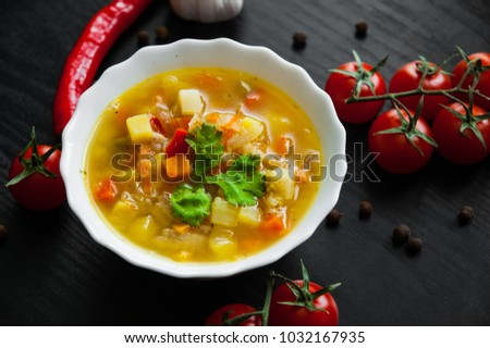 Bowl of chicken soup with vegetables on a dark wooden background