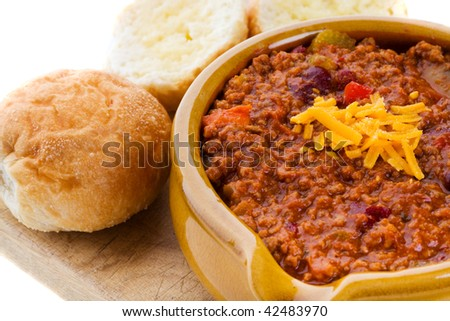 bowl of chili con carne with crusty buns and cheese - stock photo