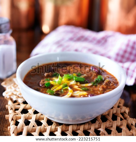 bowl of chili with scallions and grated cheese - stock photo