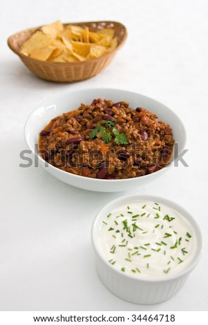 Bowl of chilli-con-carne with accompaniments of tortilla chips and sour cream with chives