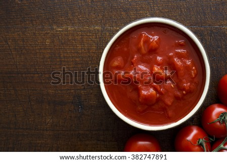 Bowl of chopped tomatoes isolated on rustic dark wood surface from above. Next to fresh whole tomatoes. Space for text. - stock photo