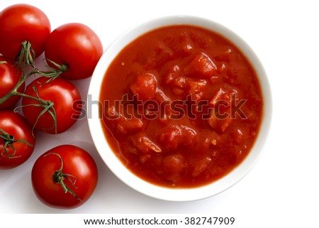 Bowl of chopped tomatoes isolated on white from above. Next to fresh whole tomatoes. - stock photo