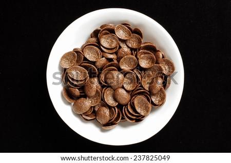 Bowl of chrispy chocolate crunch cornflakes isolated on the black background - stock photo