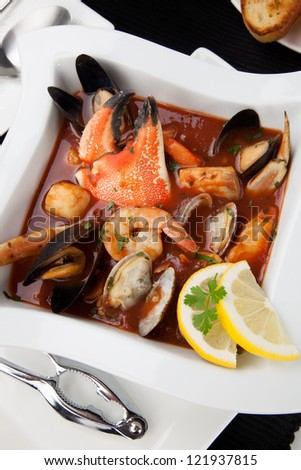 Bowl of Cioppino with Crab Claw (seafood stew) with shrimps, scallops, crabs, clams, mussels, and fish.