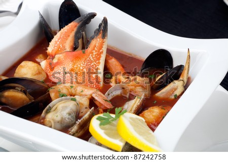 Bowl of Cioppino with Crab Claw (seafood stew) with shrimps, scallops, crabs, clams, mussels, and fish. - stock photo