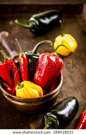 Bowl of colorful fresh cayenne chili peppers and red and yellow sweet peppers with fresh eggplant or aubergine on a rustic wooden kitchen table, high angle view - stock photo