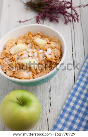 Bowl of commercial breakfast cereal topped with diced fruit together with a fresh green apple alongside a checked blue and white napkin - stock photo