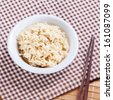 Bowl of cooked brown rices with chopsticks on table cloth - stock photo