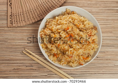 bowl of cooked rice with chopsticks and fan - stock photo