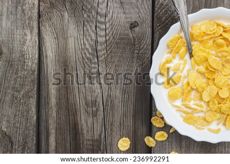 bowl of corn flakes on the old table - stock photo