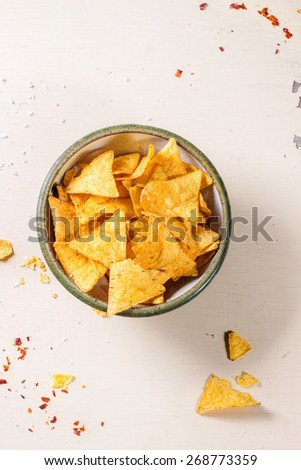Bowl of corn nachos chips over white wooden background. View from above - stock photo