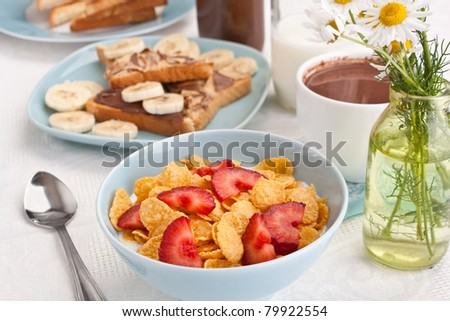 bowl of cornflakes and strawberries with yoghurt, plate of chocolate and peanut buttered toasts and a cup of hot cacao on a table