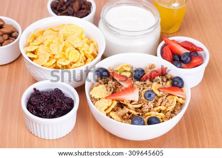 bowl of cornflakes with fresh berries and breakfast cereals, horizontal