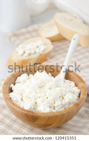 bowl of cottage cheese and slices of baguette in the background