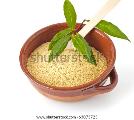 Bowl of couscous with the bay leaves on white background - stock photo