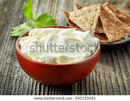 bowl of cream cheese on wooden table - stock photo