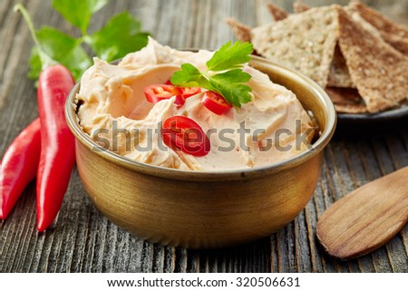 bowl of cream cheese with chili and tomato, dip sauce on wooden table - stock photo