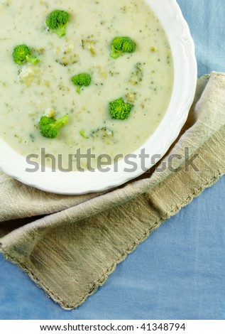 Bowl of cream of broccoli soup with a napkin on a blue tablecloth.