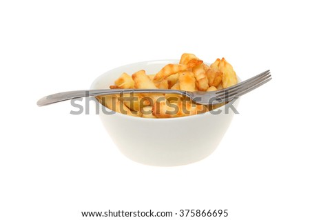 Bowl of crinkle cut chips with a fork isolated against white