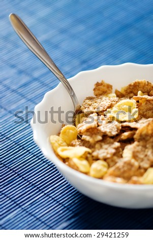 Bowl of crumbly wheat and corn cereal - stock photo