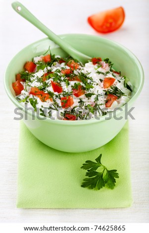 Bowl of curd with tomato and parsley - excellent healthy breakfast! - stock photo