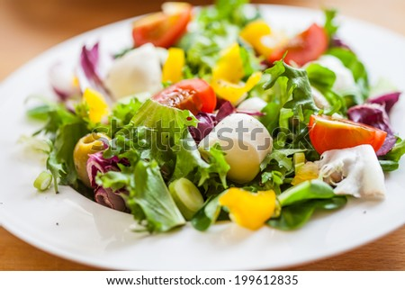 Bowl of delicious fresh salad with mozzarella and pepper
