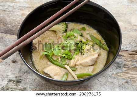 Bowl of delicious healthy creamy Thai green curry with diced chicken pieces served with chopsticks, high angle view - stock photo