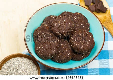 Bowl of delicious healthy dark chocolate and chia seed cookies with ingredients - stock photo