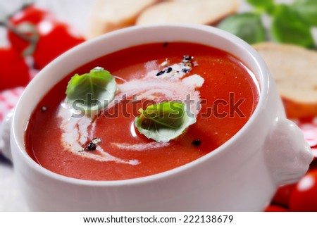 Bowl of delicious homemade tomato soup with cream and basil seasoned with pepper, closeup view - stock photo