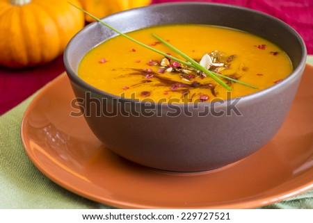 Bowl of delicious pumpkin soup garnished with fresh chives with a colorful display of ornamental gourds in the background - stock photo