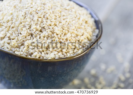 Bowl of dried bulgar wheat in rustic setting.