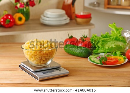 Bowl of dry pasta and digital kitchen scales on wooden table - stock photo