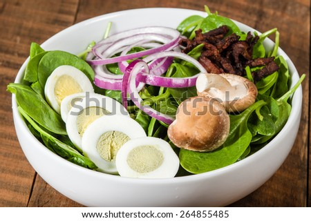 Bowl of egg and spinach salad with mushrooms and onions - stock photo