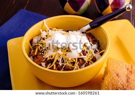 Bowl of elk meat chili with toppings and cornbread on yellow plate with blue spoon - stock photo
