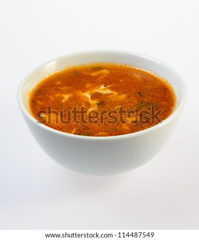Bowl of fish soup over white background - stock photo