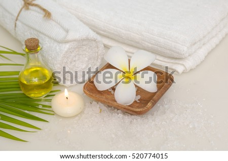 bowl of frangipani with towel and leaf ,candle on towel