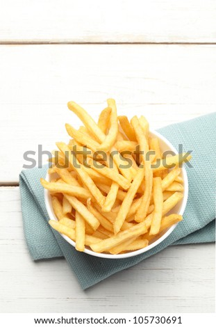 bowl of french fries on a turquoise napkin, top view - stock photo
