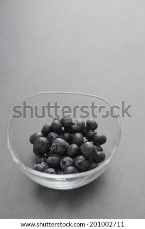 Bowl of Fresh Blueberries on dark background. Shallow depth of field. - stock photo