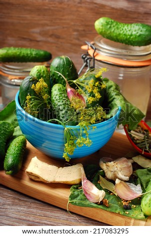 bowl of fresh cucumbers and ingredients for homemade gherkin on wooden background  - stock photo
