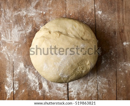 bowl of fresh dough on rustic wooden table, top view