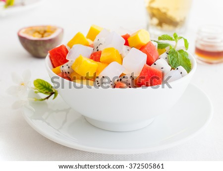 Bowl of  fresh exotic fruit salad on white summer background Healthy breakfast  - stock photo