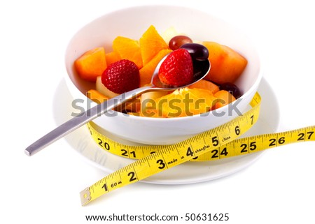 Bowl of Fresh Fruit Salad With Tape Measure - stock photo