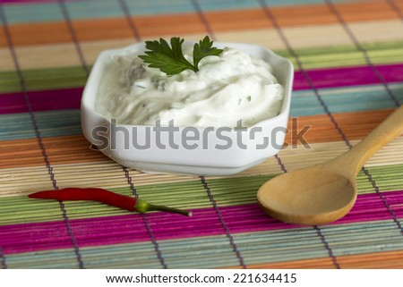 Bowl of fresh garlic dip sauce with pepper and a wooden spoon on a decorative background - stock photo