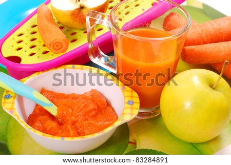 bowl of fresh grated carrot and apple puree as homemade baby food - stock photo