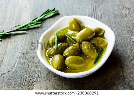 bowl of fresh green olives in olive oil on a rustic wooden texture, selective focus - stock photo
