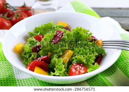 Bowl of fresh green salad on table with napkin, closeup - stock photo
