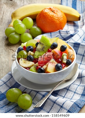Bowl of fresh healthy fruit salad on checkered tablecloth - stock photo