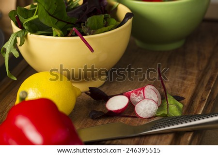 Bowl of fresh herbs with rocket and baby spinach and assorted salad ingredients including a lemon, red bell pepper and radish on a kitchen counter waiting to be prepared for dinner - stock photo