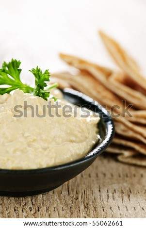 Bowl of fresh hummus dip with pita bread slices - stock photo