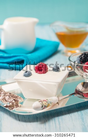 Bowl of fresh mixed berries and yogurt with farm fresh raspberries, blackberries and blueberries on a blue wooden table - stock photo